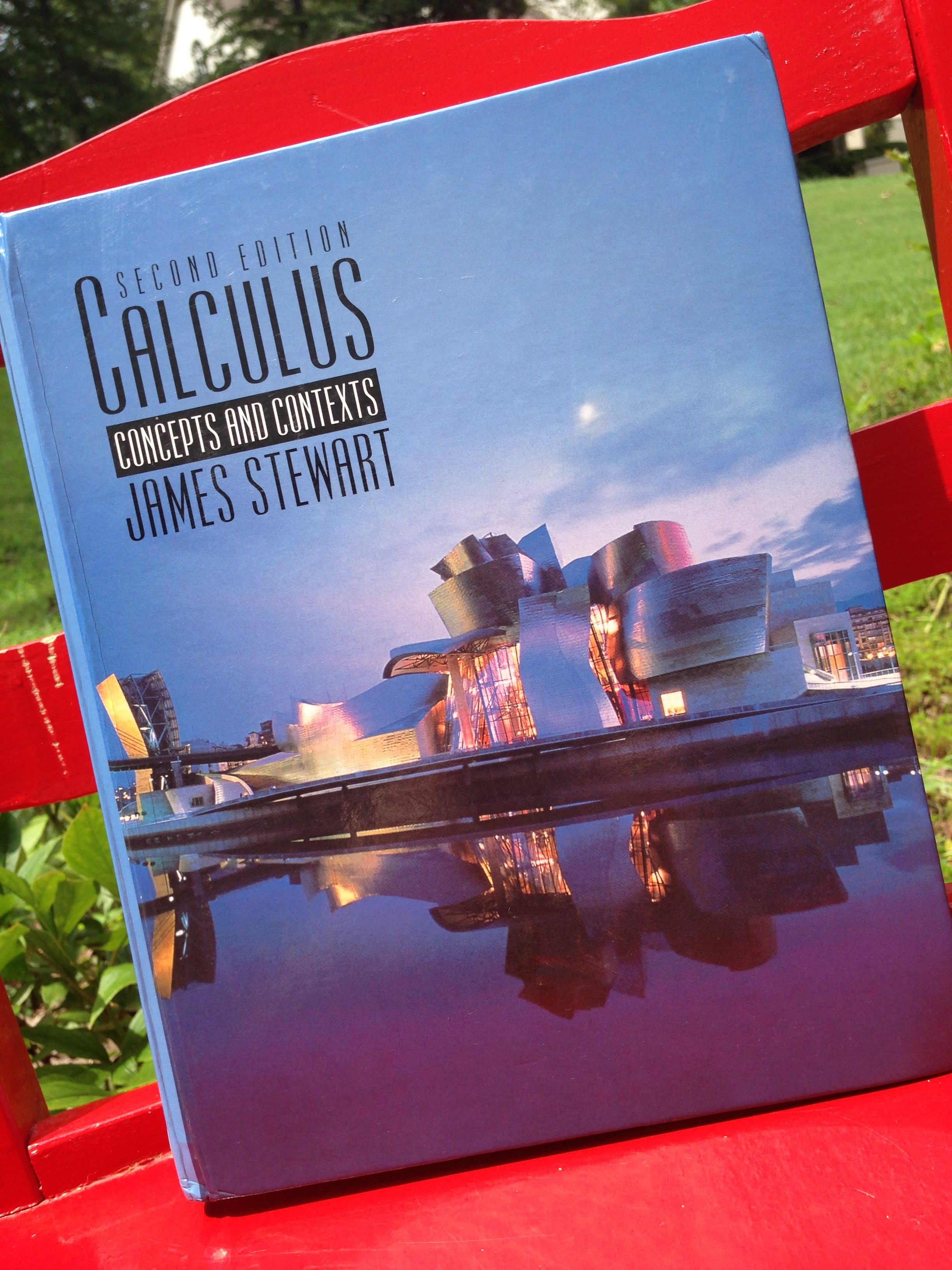 Calculus textbook with a building facing a lake and a blue sky. The textbook is sitting on a chair